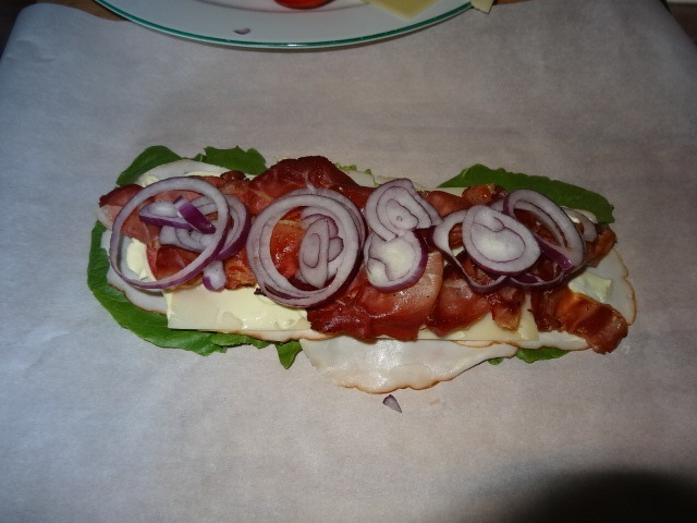 Layering the cooked bacon, meat slices, cheese, tomato, and onion slices for our bread-free subway